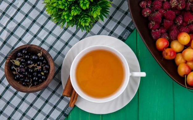 Draufsicht der tasse tee mit zimtschwarzen johannisbeeren, himbeeren und weißen kirschen auf einem karierten grünen handtuch