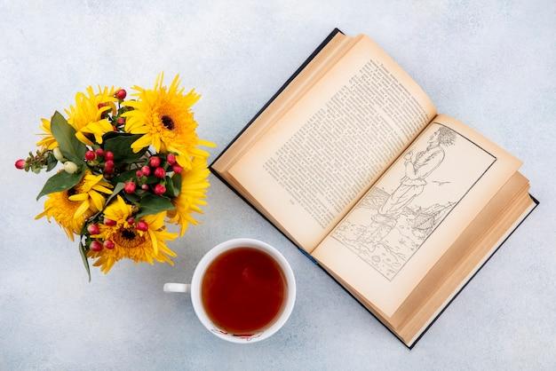 Draufsicht der tasse tee und der blumen mit offenem buch auf weiß