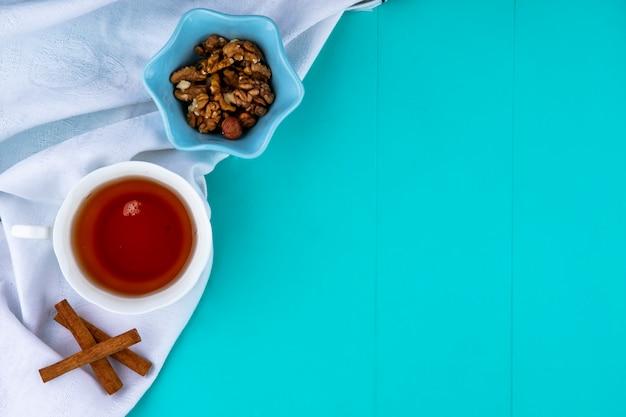 Draufsicht der tasse tee und der schüssel walnüsse mit zimt auf weißem stoff und blauem hintergrund mit kopienraum