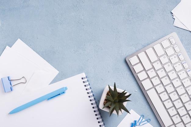 Draufsicht der tastatur auf schreibtisch mit notizbuch und saftiger anlage