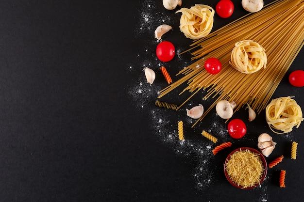 Draufsicht der teigwarenkirschtomaten-spaghettiteigwaren-knoblauchs mit kopienraum auf schwarzer oberfläche
