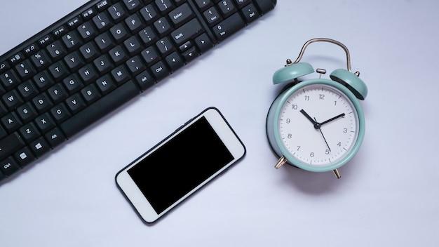 Draufsicht der telefontastatur und des weckers mit weißem hintergrund