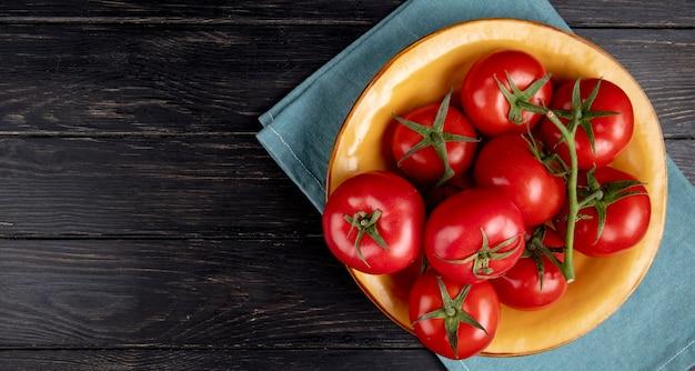 Draufsicht der tomaten in der schüssel auf blauem stoff und holz mit kopienraum