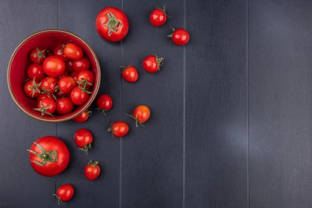 Draufsicht der tomaten in der schüssel und auf der schwarzen oberfläche