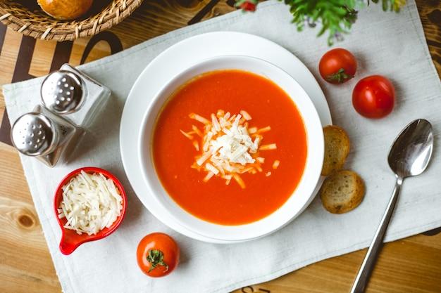 Draufsicht der tomatensuppe mit käse in einer weißen schüssel