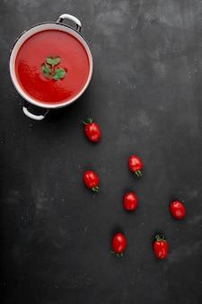 Draufsicht der tomatensuppe mit tomaten auf schwarzer oberfläche