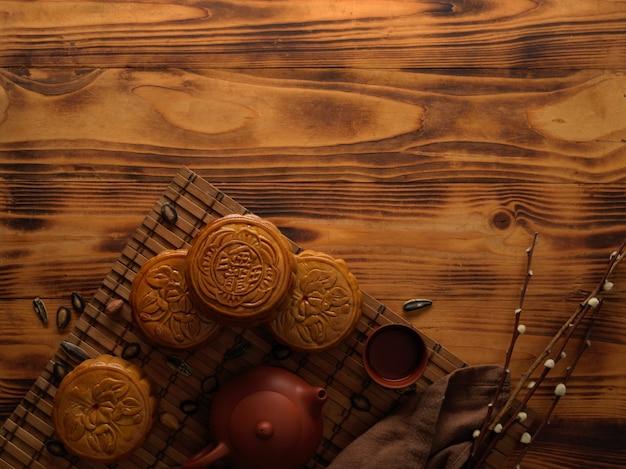 Draufsicht der traditionellen mondkuchen auf bambusmatte mit teeservice und kopienraum auf rustikalem tisch. das chinesische schriftzeichen auf dem mondkuchen steht auf englisch für