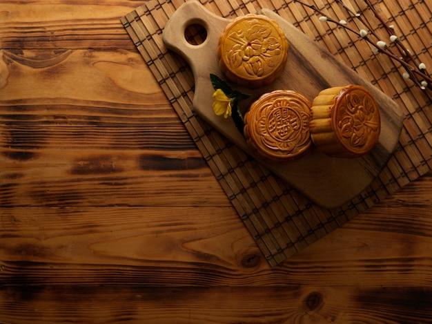 Draufsicht der traditionellen mondkuchen auf holztablett mit bambusmatte und kopienraum verziert auf rustikalem tisch. das chinesische schriftzeichen auf dem mondkuchen steht auf englisch für