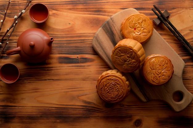 Draufsicht der traditionellen mondkuchen auf holztablett mit teeservice und kopienraum auf rustikalem tisch. das chinesische schriftzeichen auf dem mondkuchen steht auf englisch für