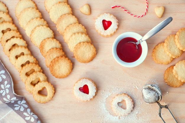 Draufsicht der traditionellen weihnachtslinzerplätzchen gefüllt mit erdbeermarmelade auf holzbrett.
