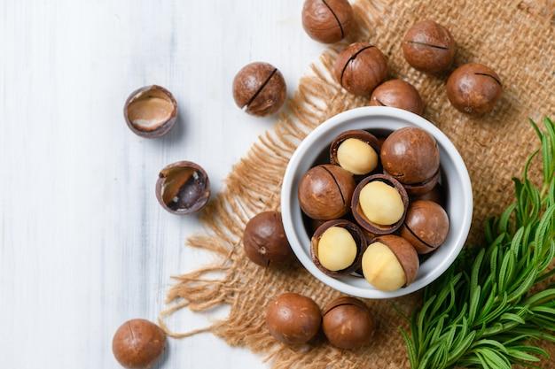 Draufsicht der trockenen gerösteten macadamia-nuss in der weißen tasse auf holzhintergrund,