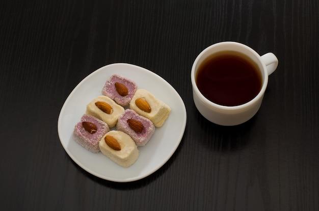 Draufsicht der türkischen freude mit mandeln und tasse kaffee, schwarze tabelle