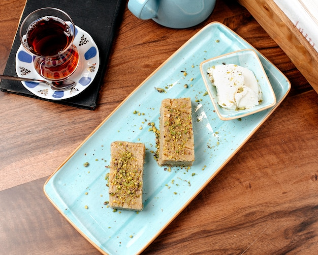 Draufsicht der türkischen süßigkeiten baklava mit pistazie serviert mit eis auf einer platte