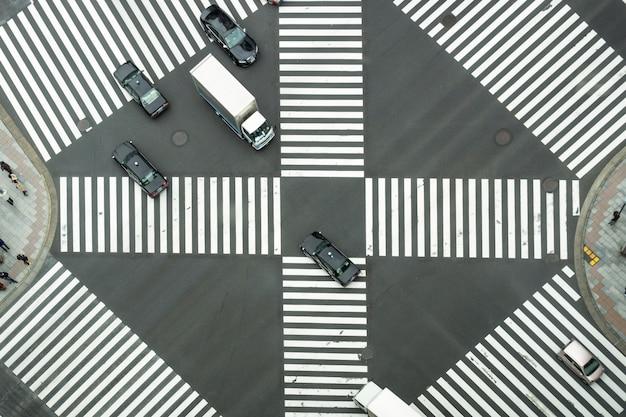 Draufsicht der undefinierten japanischen leutemenge gehen, um die straße zwischen den gebäuden zu kreuzen