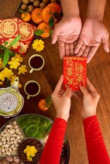 Draufsicht der unerkennbaren geernteten frau, die dem mann das geschenk des chinesischen neujahrsfests übergibt