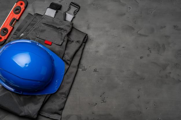 Draufsicht der uniform des bauarbeiters auf hölzernem hintergrund