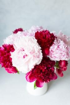 Draufsicht der vase mit blumenstrauß der schönen pfingstrosen auf tisch im raum, nahaufnahme. blühen. pfingstrose.