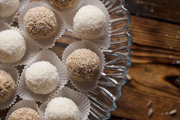 Draufsicht der vegetarischen energieball-bonbons der kokosnuss und der erdnuss auf holztisch