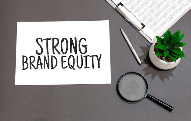 Draufsicht der vergrößerungsglas-rechneranlage und des notizbuchs geschrieben mit strong brand equity-zeichen