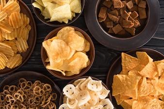 Draufsicht der verschiedenen Junk-Food und Snacks auf Holztisch