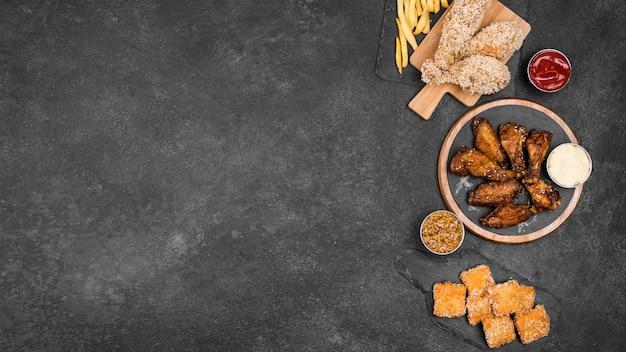 Draufsicht der vielzahl von gebratenem huhn mit pommes frites und kopienraum