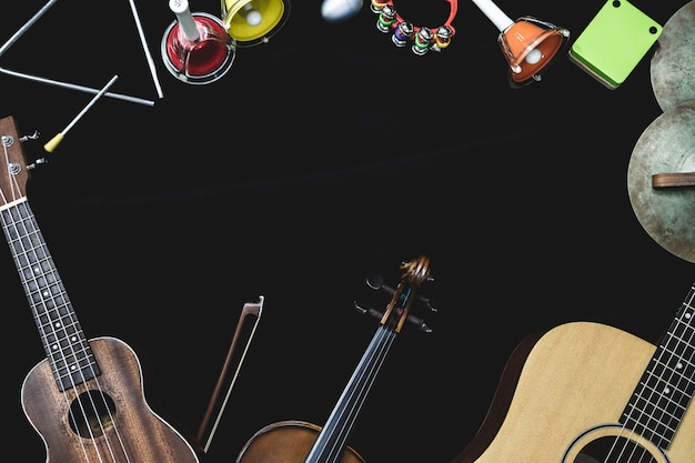Draufsicht der violingitarre und der ukulele mit schlaginstrumenten auf dem schwarzen hintergrund