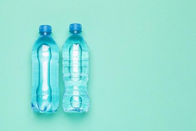 Draufsicht der wasserflaschenebene lage über farbpapierhintergrund