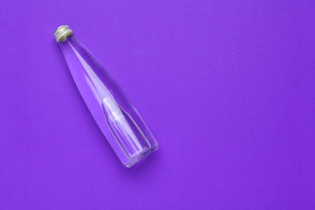 Draufsicht der wasserflaschenebene lage über purpurroten hintergrund