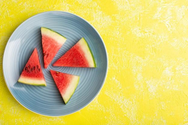 Draufsicht der wassermelonenscheiben innerhalb der blauen platte auf der gelben oberfläche