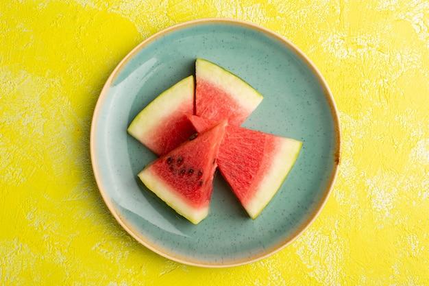 Draufsicht der wassermelonenscheiben innerhalb der grünen platte auf der gelben oberfläche