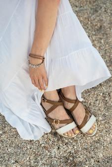Draufsicht der weiblichen füße in den sandalen am sandstrand.