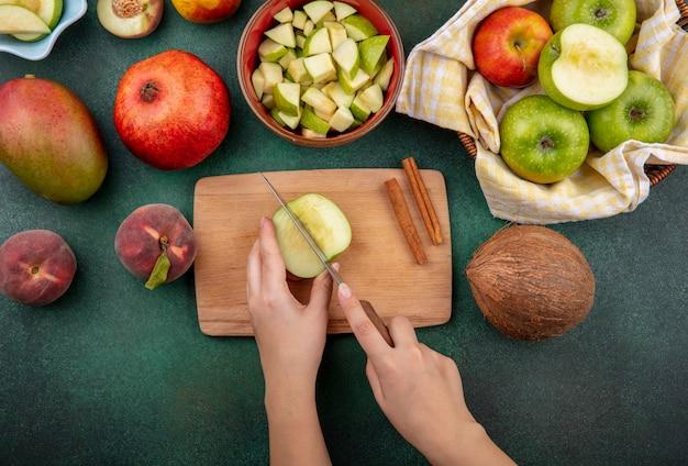 Draufsicht der weiblichen hände, die apfel in scheiben auf küchenbrett mit messer mit zimtstangen kokosnusspfirsich lokalisiert auf grün schneiden