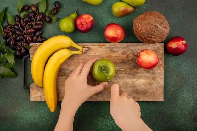 Draufsicht der weiblichen hände, die apfel mit messer und bananenpfirsich auf schneidebrett und birnen-kokosnuss-traubenpfirsich auf grünem hintergrund schneiden