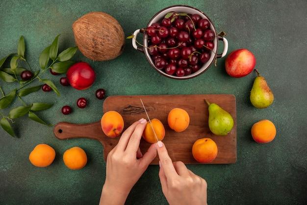 Draufsicht der weiblichen hände, die aprikose mit messer und birne auf schneidebrett und kirschen in schüssel mit pfirsich-kokosnuss und blätter auf grünem hintergrund schneiden