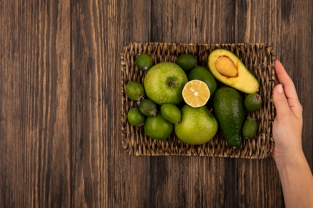 Draufsicht der weiblichen hände, die ein weidentablett mit frischen früchten wie grünen äpfeln feijoas limetten auf einer holzwand mit kopierraum halten