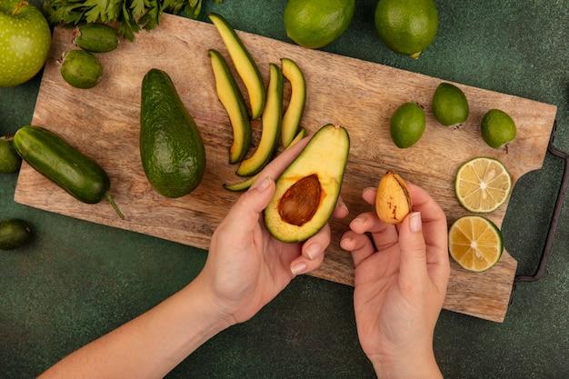 Draufsicht der weiblichen hände, die eine avocado in einer hand und seine grube in der anderen hand auf einem hölzernen küchenbrett mit limettenfeijoas und grünen äpfeln lokalisiert auf einer grünen oberfläche halten