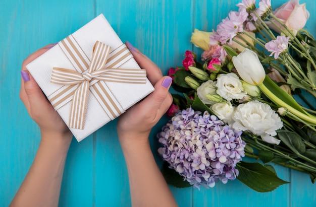 Draufsicht der weiblichen hände, die eine geschenkbox mit wundervollen frischen blumen wie rosengartenzia-tulpengänseblümchen lokalisiert auf einem blauen hölzernen hintergrund halten