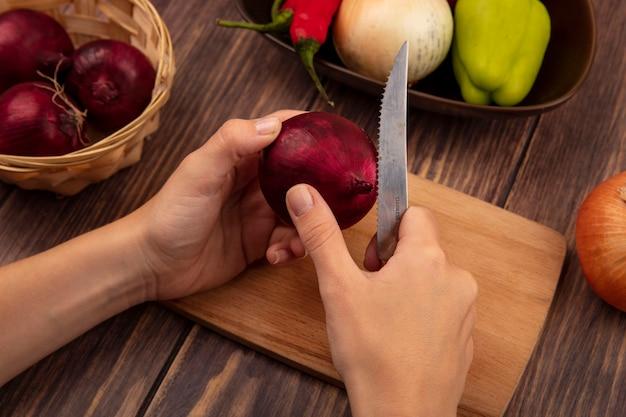 Draufsicht der weiblichen hände, die eine rote zwiebel auf einem hölzernen küchenbrett mit messer auf einer holzwand schneiden