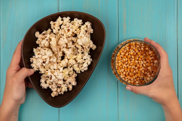 Draufsicht der weiblichen hände, die eine schüssel der leckeren popcorns in einer hand und in der anderen hand eine schüssel der popcornkerne auf einem blauen holztisch halten