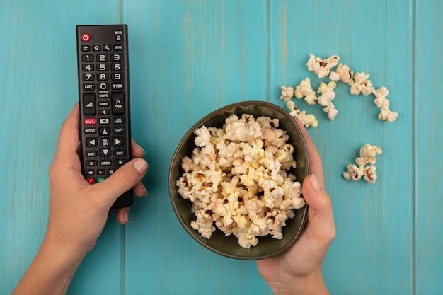 Draufsicht der weiblichen hände, die eine schüssel gewürzte popcorns mit popcorns lokalisiert auf einem blauen holztisch halten