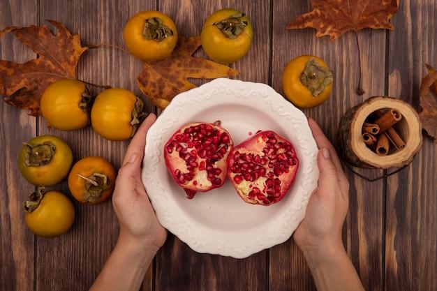 Draufsicht der weiblichen hände, die eine schüssel granatäpfel mit kaki-früchten lokalisiert auf einem holztisch halten