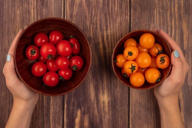 Draufsicht der weiblichen hände, die eine schüssel mit frischen kirschroten tomaten in einer hand und in der anderen hand eine schüssel mit orangefarbenen kirschtomaten auf einer holzoberfläche halten