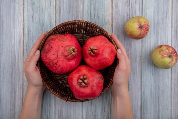 Draufsicht der weiblichen hände, die einen eimer mit roten frischen granatäpfeln mit äpfeln lokalisiert auf einem grauen hölzernen hintergrund halten