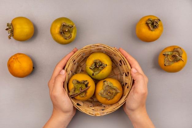 Draufsicht der weiblichen hände, die einen eimer von kaki-früchten mit kaki-früchten isoliert halten