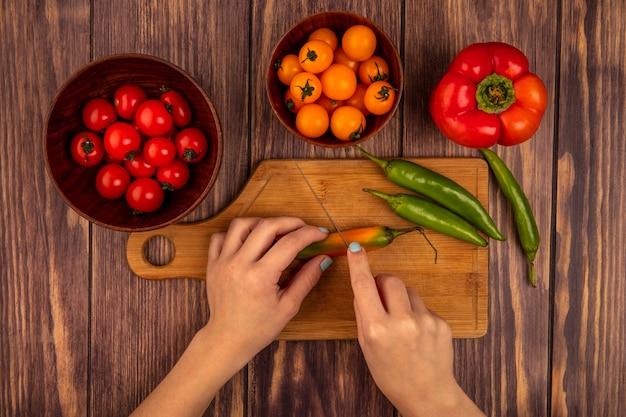 Draufsicht der weiblichen hände, die einen frischen pfeffer auf einem hölzernen küchenbrett mit messer mit kirschtomaten auf einer hölzernen schüssel auf einer hölzernen oberfläche schneiden