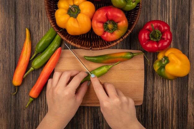 Draufsicht der weiblichen hände, die einen frischen pfeffer auf einem hölzernen küchenbrett mit messer mit paprika schneiden, die auf einem hölzernen hintergrund lokalisiert werden