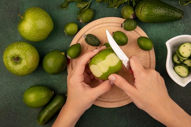 Draufsicht der weiblichen hände, die einen grünen frischen apfel mit messer auf einem hölzernen küchenbrett mit limetten, feijoas und grünen äpfeln schälen, die auf einer grünen oberfläche lokalisiert werden