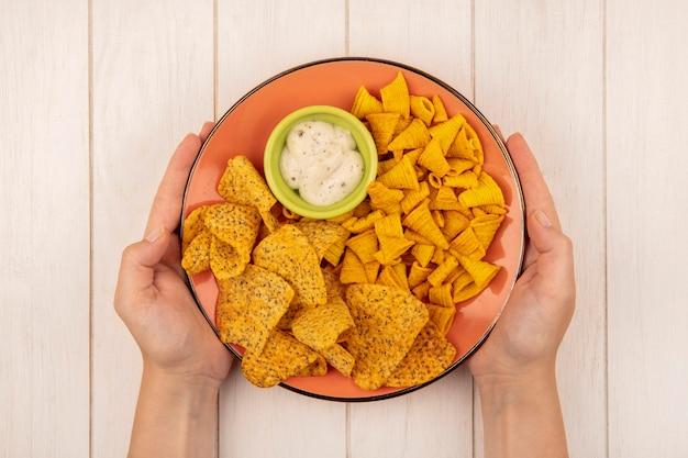 Draufsicht der weiblichen hände, die einen orangefarbenen teller mit würzigen knusprigen chips mit soße auf einer grünen schüssel auf einem beigen holztisch halten