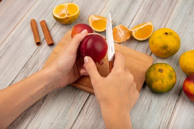 Draufsicht der weiblichen hände, die einen pfirsich auf einem hölzernen küchenbrett mit messer mit mandarinen hacken lokalisiert auf einem grauen hölzernen hintergrund hacken