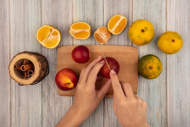 Draufsicht der weiblichen hände, die einen pfirsich auf einem hölzernen küchenbrett mit messer mit mandarinen schneiden, die auf einer grauen holzwand isoliert werden